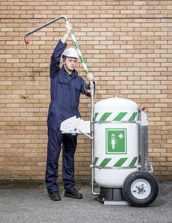 Muž montujúci mobilnú bezpečnostnú sprchu so 114l zásobníkom vody na kolesách