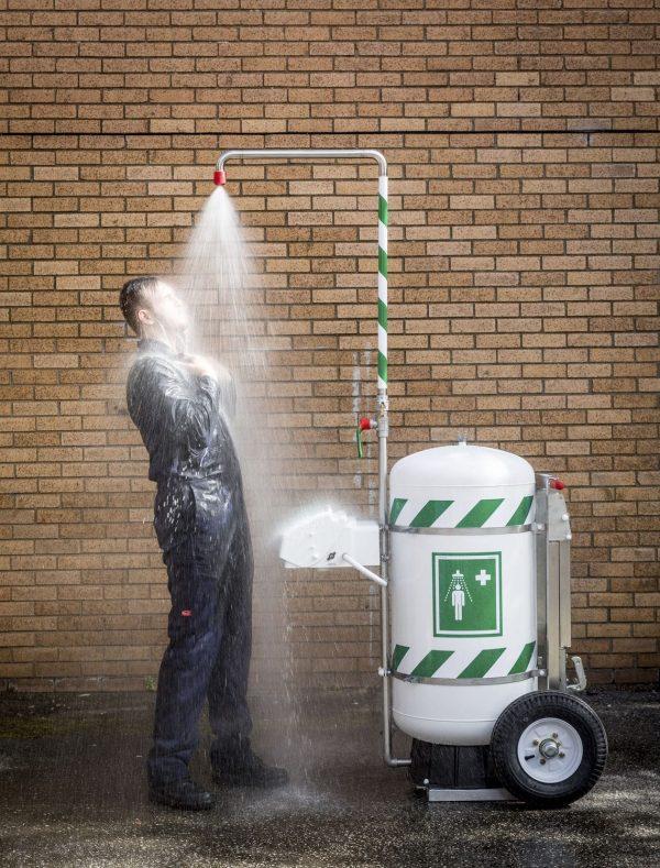 Muž sprchujúci sa pod mobilnou bezpečnostnou sprchou so 114l zásobníkom vody na kolesách