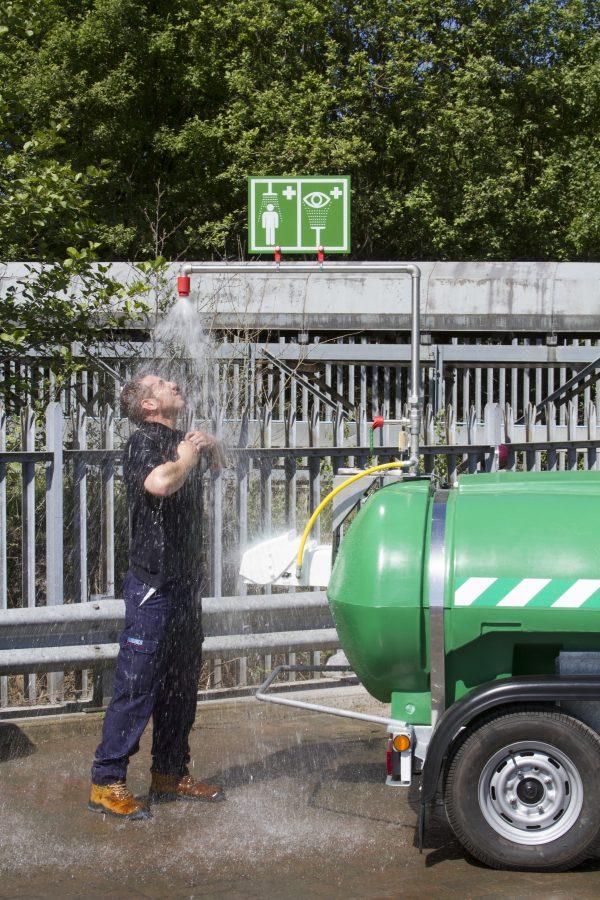 Muž sprchujúci sa pod zelenou mobilnou sprchou Hughes STD-MH-P so zásobníkom na kolesách