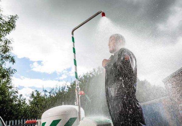 Muž stojaci v záhrade pod striekajúcou mobilnou bezpečnostnou sprchou so zásobníkom vody objem 114l