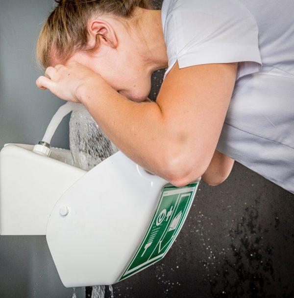 žena vykonávajúca výplach očí prostredníctvom fontány očnej havarijnej sprchy STD 45G s otvoreným poklopom a nalepeným piktogramom